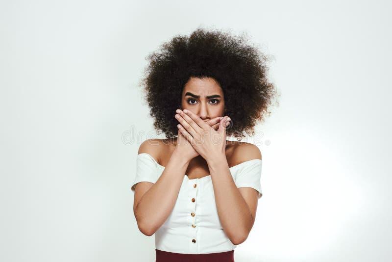 Zeg nooit teveel De jonge afro Amerikaanse vrouw met krullend haar behandelt mond met handen en bekijkt camera terwijl royalty-vrije stock afbeelding