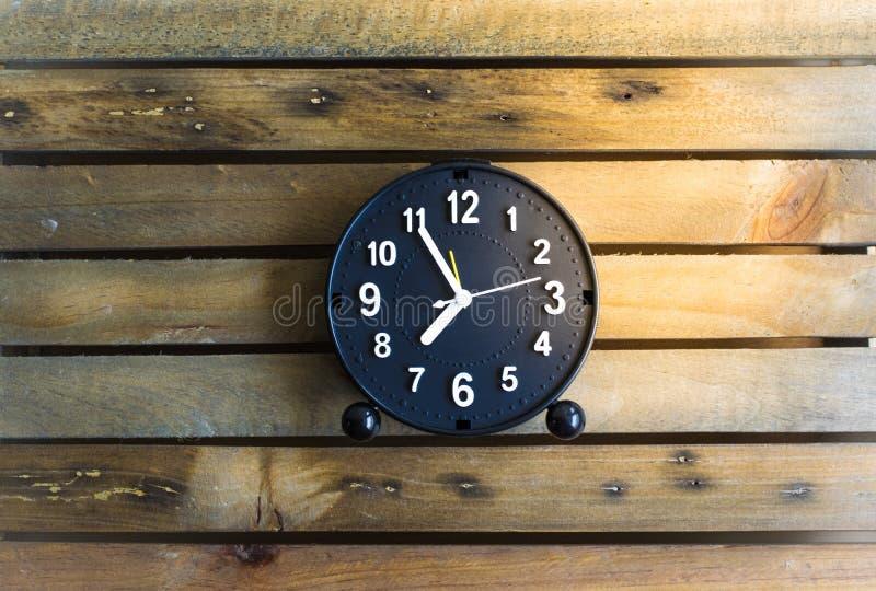 Zegar na drewno deski tle używać tapetę dla edukaci, biznesowa fotografia Bierze notatkę produkt dla książki z papierem i obje fotografia royalty free