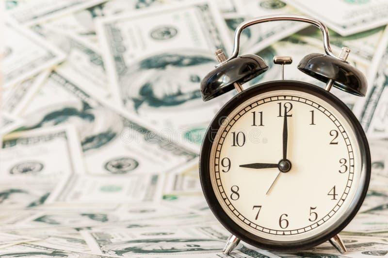 Zegar na gotówkowym miesiąca dolarowego rachunku wzoru tle zdjęcia stock