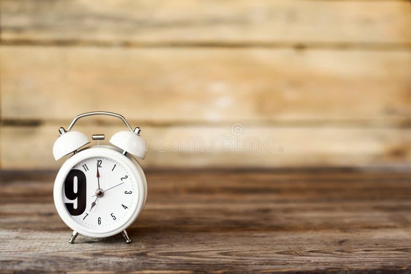 Zegar przy 7 O ` zegarem w ranku z rocznika stylu budzikiem na drewnianym stole obraz royalty free