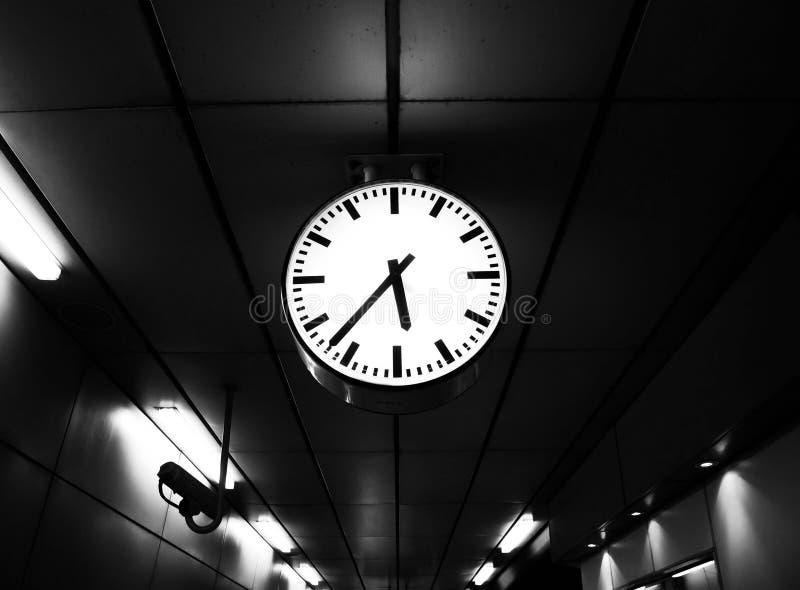 Zegar przy staci kolejowej przedstawieniem czas podczas gdy ludzie czeka pociąg pracować biurowego białego czarnego biel zdjęcie royalty free