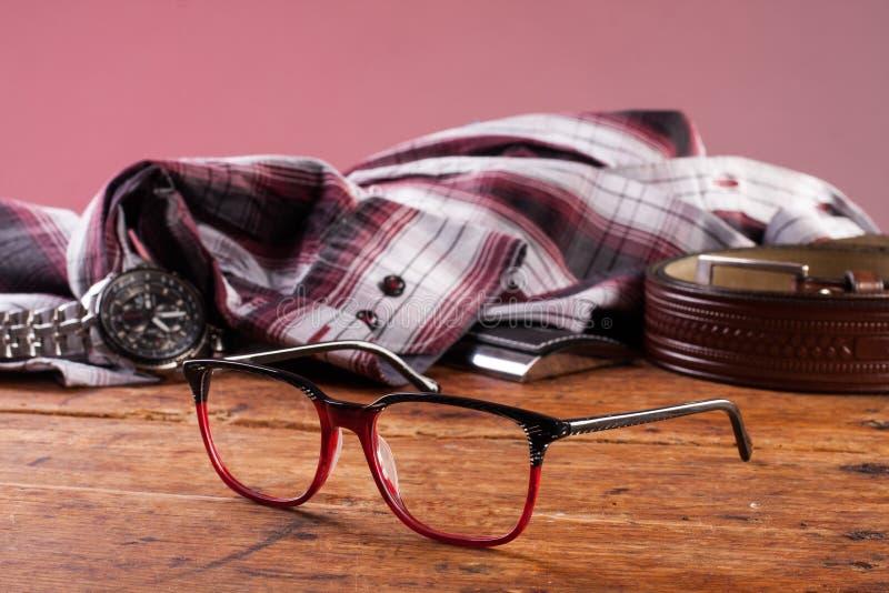 Zegar, szkła i koszula na drewnianym stole, fotografia stock