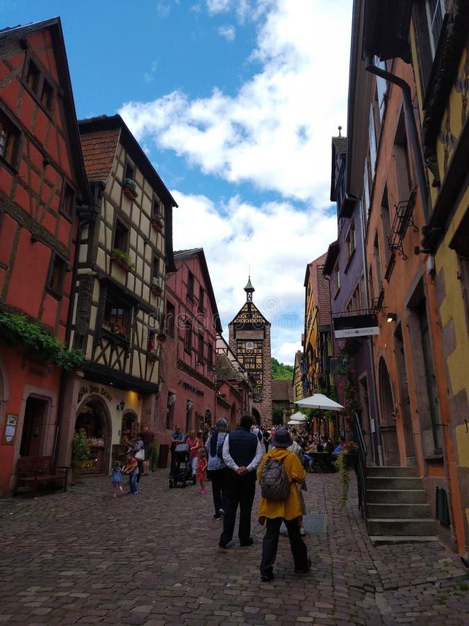 Zegarowy wierza, tradycyjni domy z kolorowymi fasadami i pochylanie dachy w Riquewihr, Francja zdjęcia royalty free