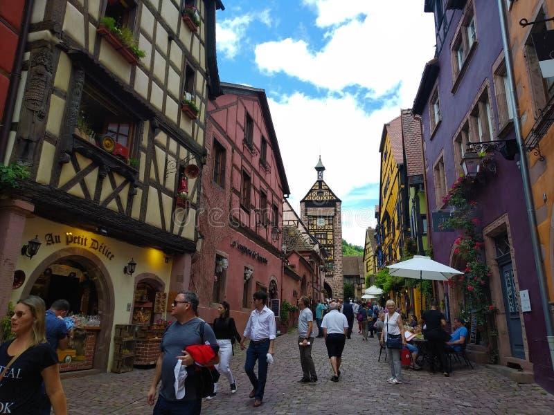 Zegarowy wierza, tradycyjni domy z kolorowymi fasadami i pochylanie dachy w Riquewihr, Francja obraz royalty free