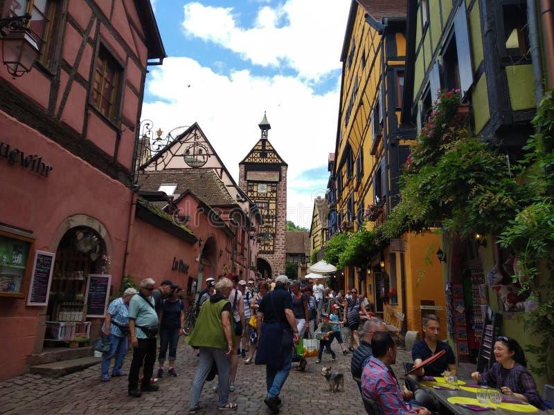 Zegarowy wierza, tradycyjni domy z kolorowymi fasadami i pochylanie dachy w Riquewihr, Francja obrazy royalty free
