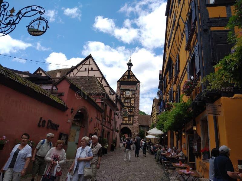 Zegarowy wierza, tradycyjni domy z kolorowymi fasadami i pochylanie dachy w Riquewihr, Francja zdjęcia stock