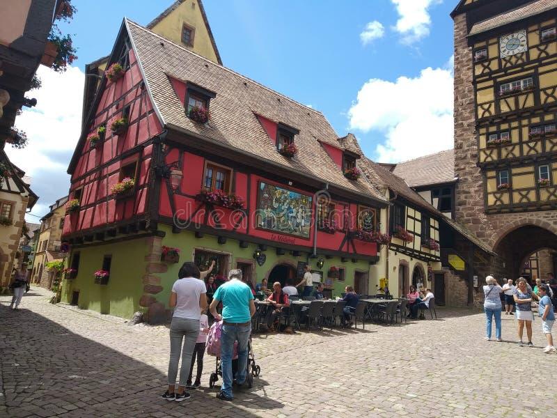 Zegarowy wierza, tradycyjni domy z kolorowymi fasadami i pochylanie dachy w Riquewihr, Francja zdjęcie stock