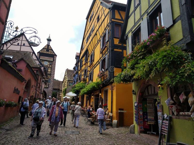 Zegarowy wierza, tradycyjni domy z kolorowymi fasadami i pochylanie dachy w Riquewihr, Francja zdjęcie royalty free