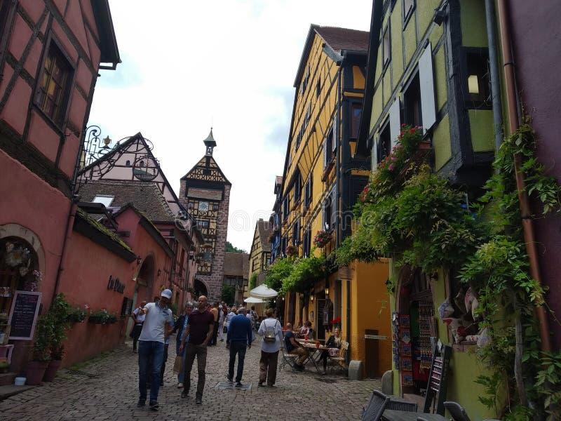 Zegarowy wierza, tradycyjni domy z kolorowymi fasadami i pochylanie dachy w Riquewihr, Francja obraz stock