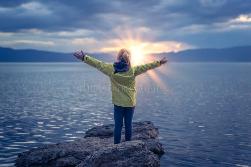 Zegevierend meisje op meerkust stock foto