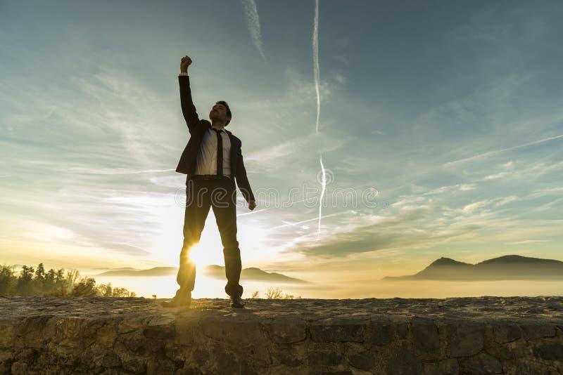Zegevierend zakenman die een nieuwe dag begroeten stock foto's