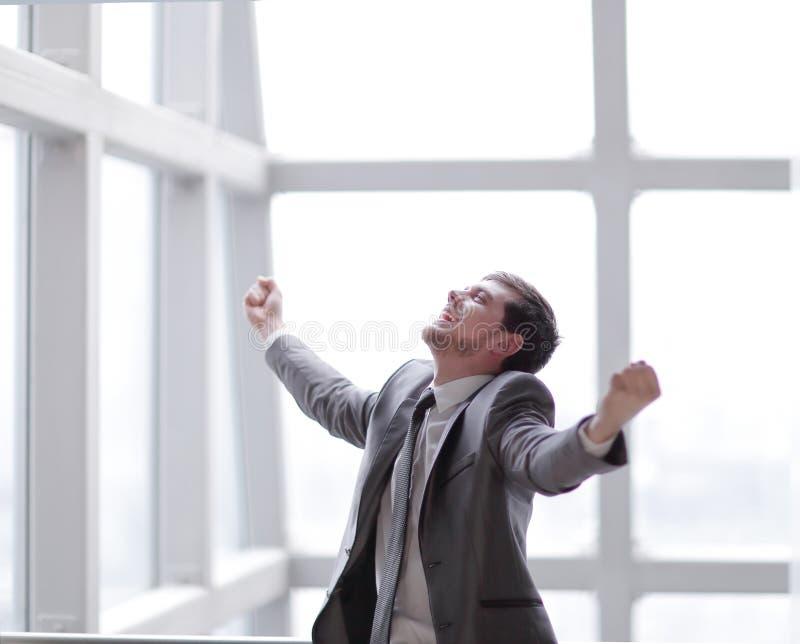 Zegevierend zakenman die zich in het bureau bevinden Foto met exemplaarruimte stock afbeeldingen