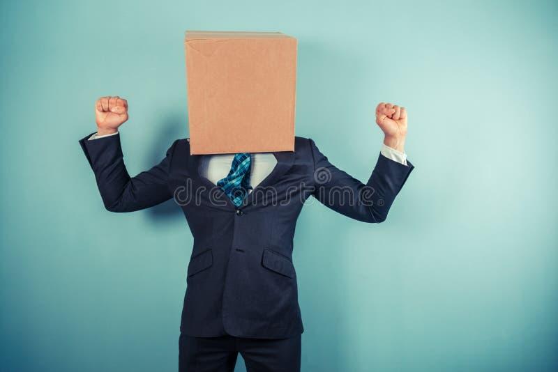 Zegevierend zakenman met doos op hoofd royalty-vrije stock afbeelding