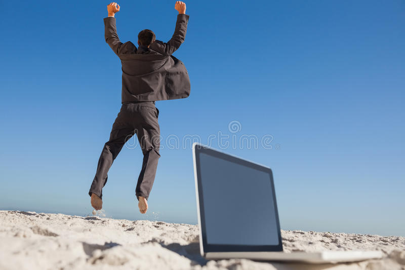 Zegevierende zakenman die verlatend zijn laptop springen royalty-vrije stock foto