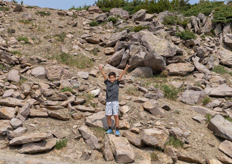 Zehn Jährige Amerasian-Junge, der enthusiastisch im Berg Rainier National Park, Washington aufwirft lizenzfreies stockfoto