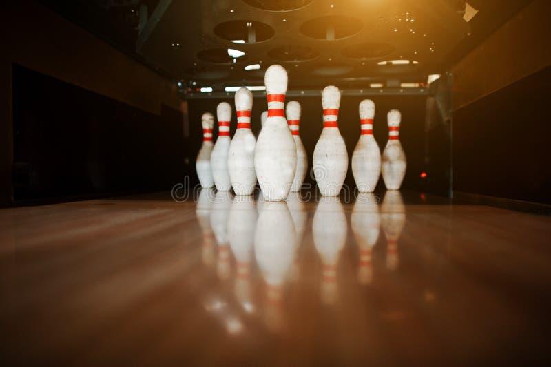 Zehn weiße Stifte in einem Bowlingbahnweg stockfotografie