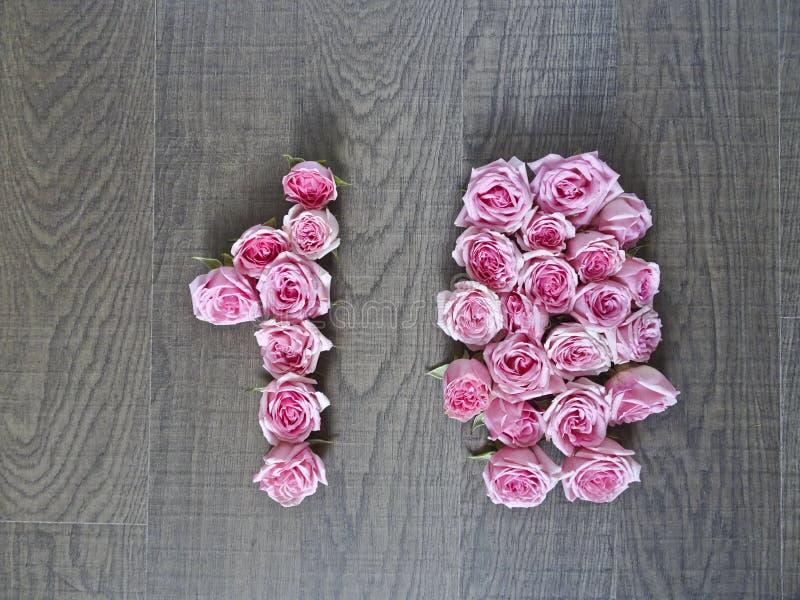 10, zehn - Weinlesezahl von rosa Rosen auf dem Hintergrund des dunklen Holzes stockfotografie