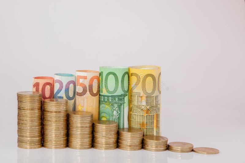 Zehn, zwanzig, fünfzig, hundert, zweihundert und Münzeneuro rollten Rechnungsbanknoten auf weißem Hintergrund Histogramm vom Euro lizenzfreie stockbilder