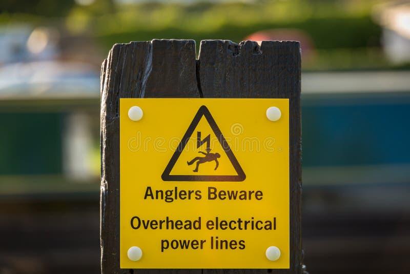 Zeichen: Angler passen, obenliegende Linien der elektrischen Leistung auf stockbilder