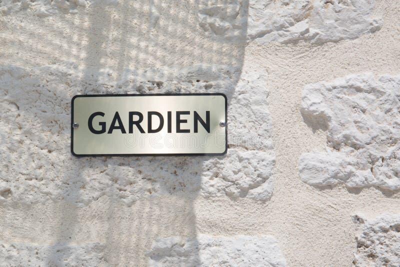 Zeichen auf dem Errichten im Freien gardien bedeutet Wächterhausmeisterservice auf Französisch stockbild
