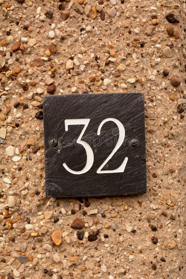 Zeichen der Hausnummer 32 auf Wand stockfoto