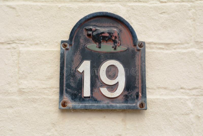 Zeichen der Hausnummer 19 mit Kuh auf Wand lizenzfreie stockfotos