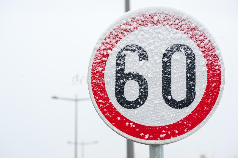 Zeichen der Verkehrsstraßen-Höchstgeschwindigkeit 60 auf der Straße bedeckt mit Schnee Gefahrenim glatten Wintersaisonabschluß ob lizenzfreie stockfotografie
