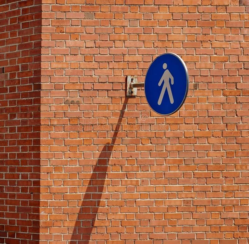 Zeichen des Fußgängers nur, das an der Backsteinmauer mit einem langen Schatten hängt stockfotos