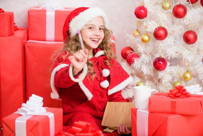 Zeichen für Sankt Wunschzettel I war gutes Mädchen das ganze Jahr Mädchenkleinkindgriffstift und -papier nahe Weihnachtsbaumschre stockfotografie