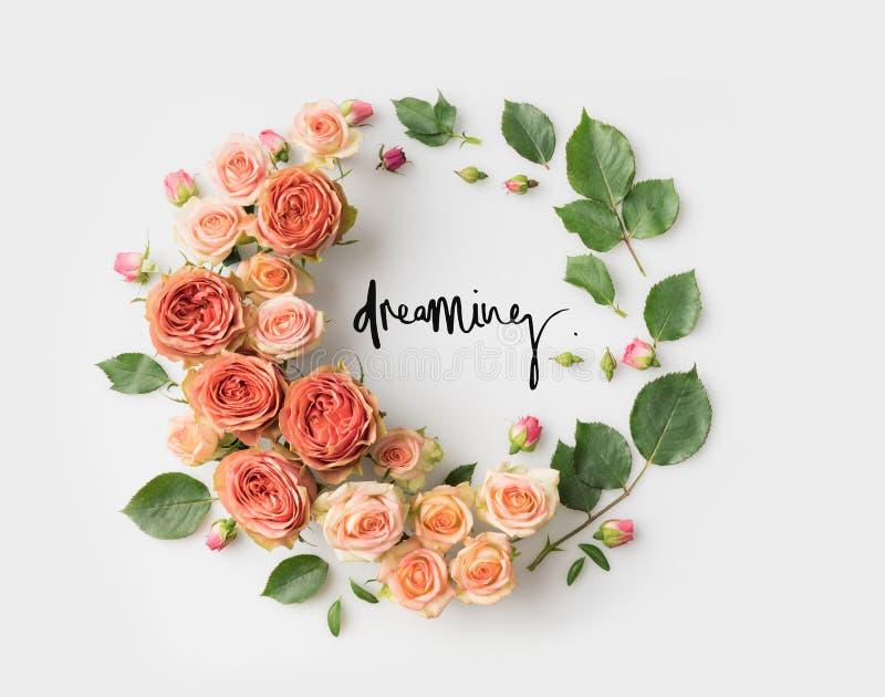 Zeichen innerhalb des rosa Blumenkranzes mit den Blättern, Knospen und Blumenblättern TRÄUMEN lokalisiert auf Weiß stockfoto