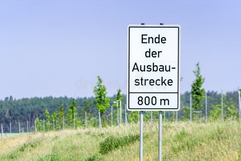 Zeichen mit den deutschen Wörtern 'Ende der Erweiterung 'als Zeichen des Endes einer Landstraße stockbild