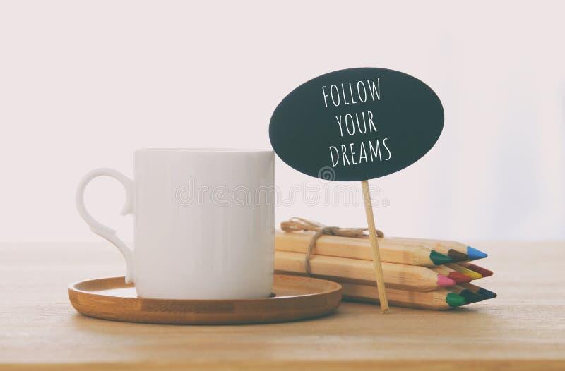 Zeichen mit Text: FOLGEN Sie IHREN TRÄUMEN nahe bei Tasse Kaffee über Holztisch lizenzfreies stockfoto