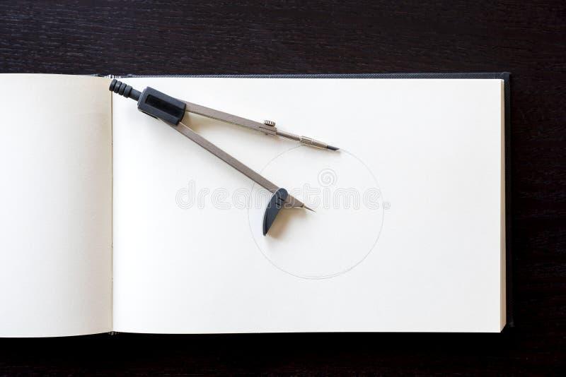 Zeichenzirkel über zu personifizieren dem Notizbuch stockbild