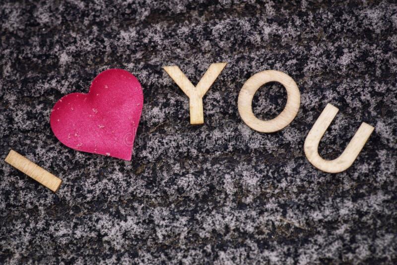 Zeichnen eines Herzens auf dem schneebedeckten Valentinsgruß `s Tag Herz des Rosas im Schnee mit den Buchstaben süß Valentinsgruß stockfoto