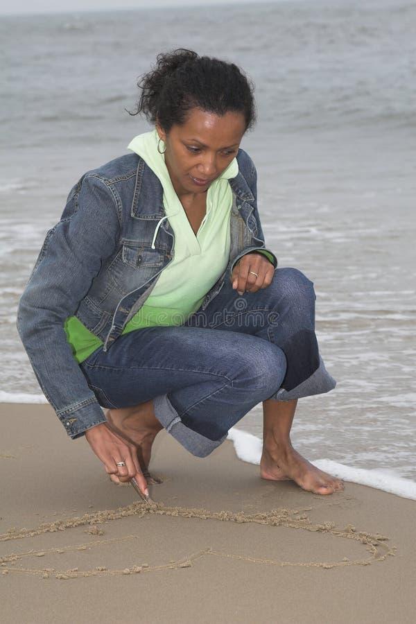 Zeichnen eines Inneren im Sand stockbilder