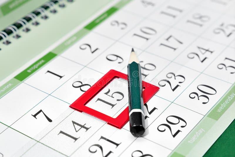 Zeichnen Sie auf dem Kalender mit einem Bookmark auf dem Datum an stockbild