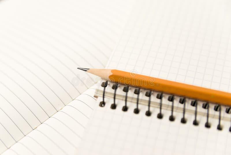 Zeichnen Sie auf den Seiten eines offenen Notizbuches für Aufzeichnungen an stockbild