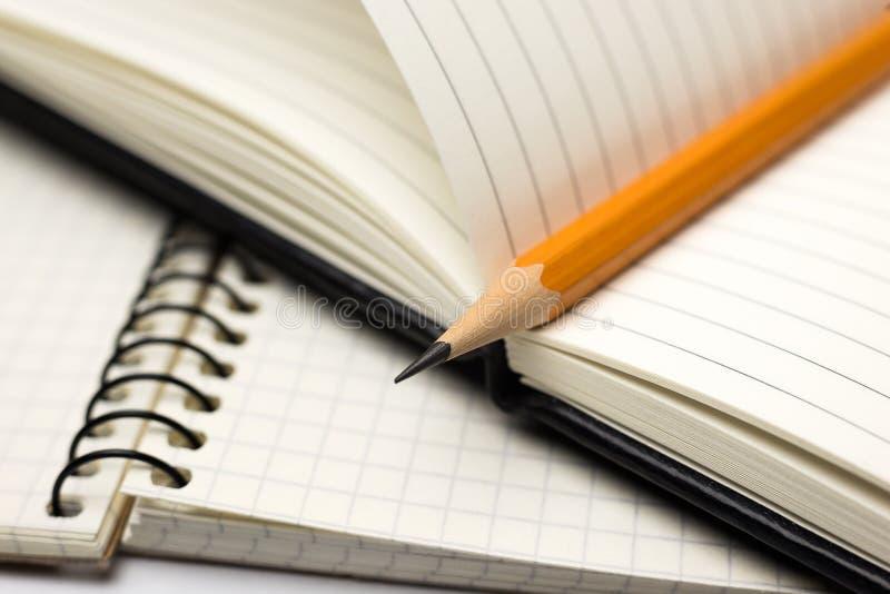Zeichnen Sie auf den Seiten eines offenen Notizbuches für Aufzeichnungen an stockfoto