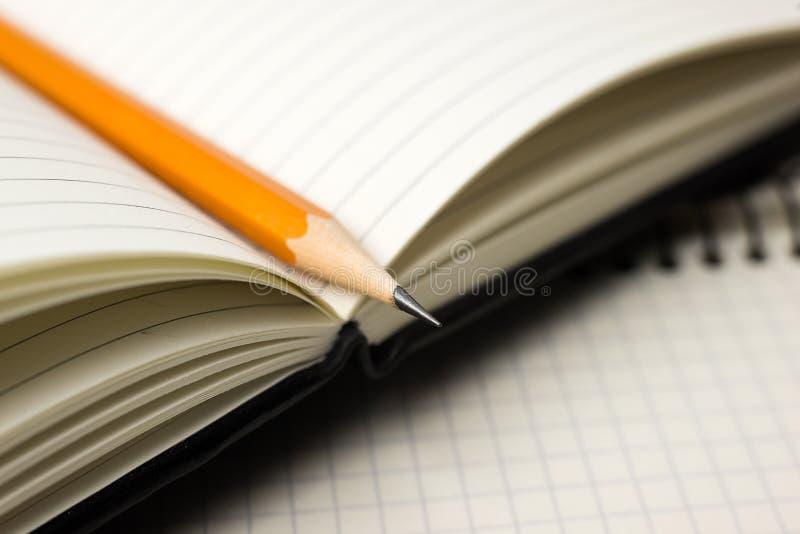 Zeichnen Sie auf den Seiten eines offenen Notizbuches für Aufzeichnungen an stockbilder