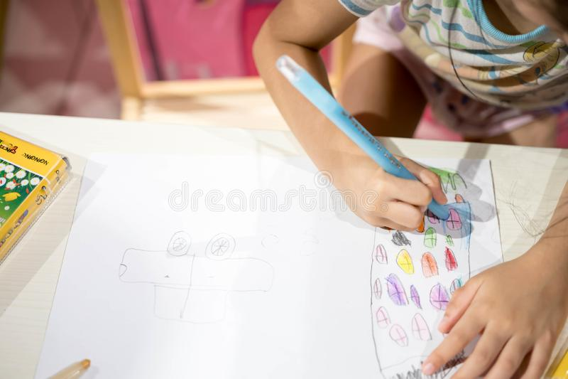 Zeichnender Farbton des Kinderschreibens auf Papier unter Verwendung des Zeichenstifts lizenzfreies stockbild