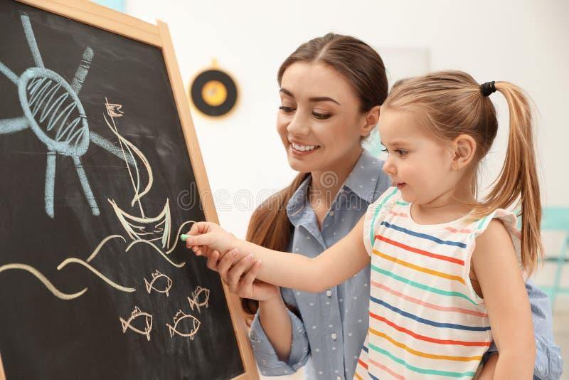 Zeichnung der Kindergärtnerin und des kleinen Kindes auf Tafel Lernen und Spielen lizenzfreie stockfotos