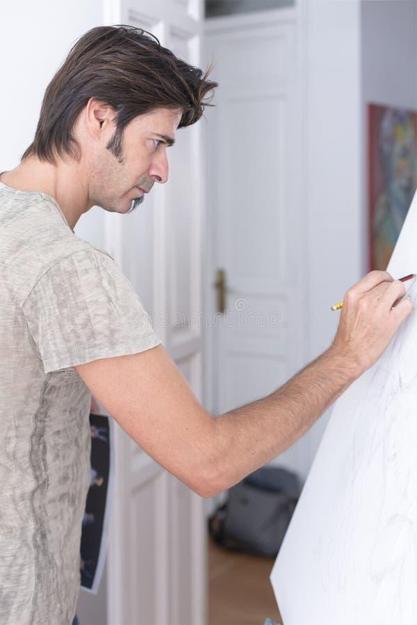 Zeichnung des jungen Mannes auf Segeltuch - Malereisitzung stockfoto