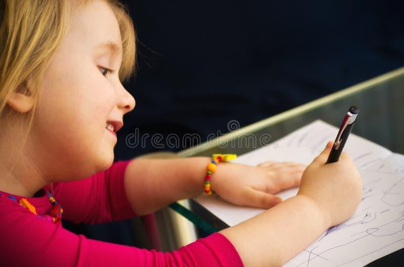 Zeichnung des kleinen Mädchens mit Stift lizenzfreie stockfotos