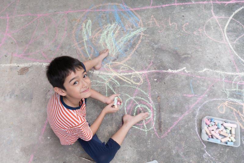 Zeichnung und Farbton des kleinen Jungen durch Kreide auf der Grundkunsttätigkeit lizenzfreie stockbilder