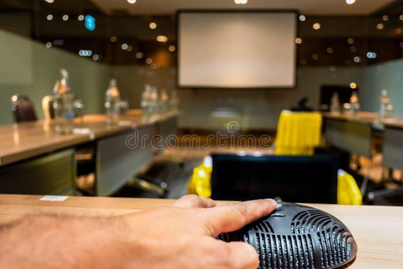 Zeigefinger, der die Knopfmikrofon Vdo-Konferenz drückt lizenzfreies stockbild