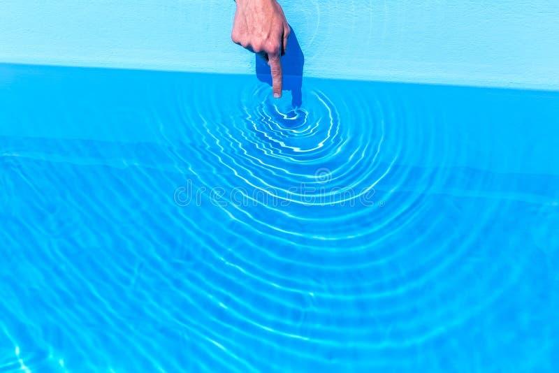 Zeigefinger, der Wellen wie Kreise im Swimmingpool macht stockfotografie