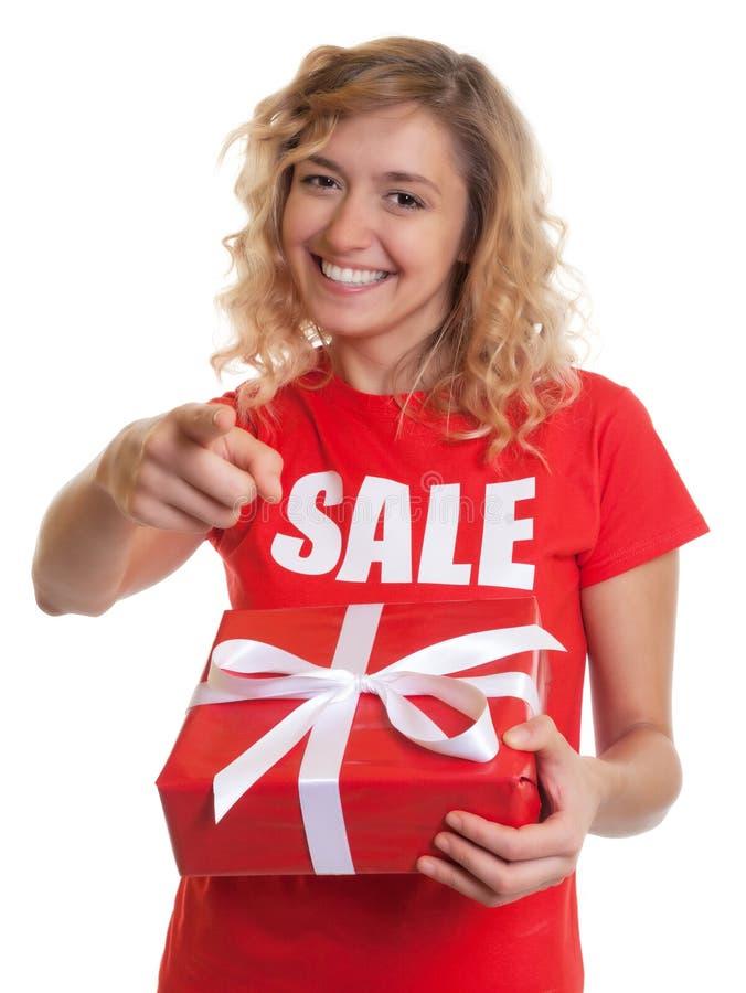 Zeigefrau mit dem blonden Haar und Geschenk in einem Verkaufhemd stockbild