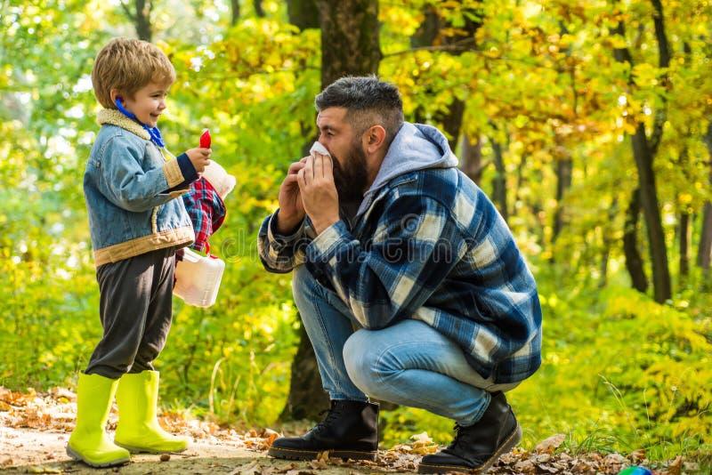 Zeigen des kranken Vaters, der am Herbstpark niest Kalte Grippe-Saison, laufende Nase Hallo Herbsttschüss Sommer Netter Junge mit stockbild