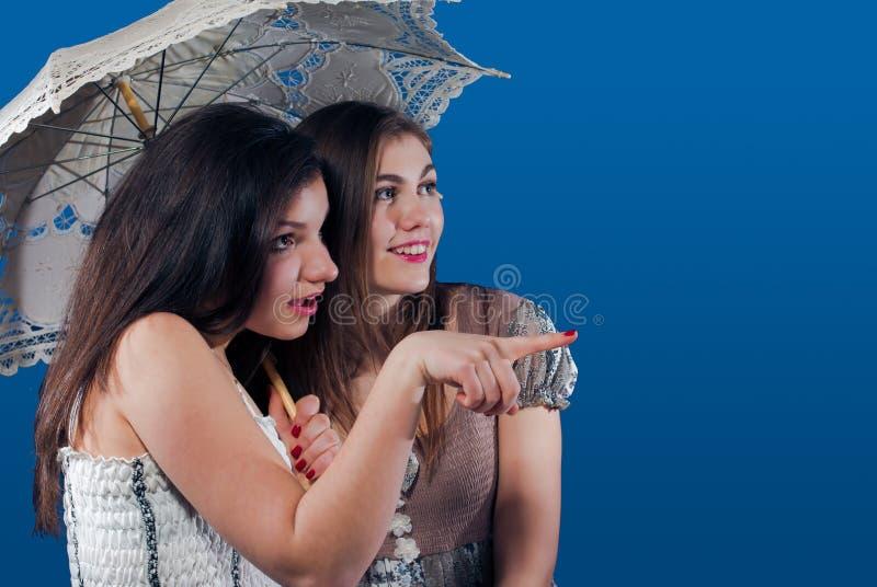 Zeigen unter lächelnde junge Frau des Regenschirmes zwei lizenzfreie stockfotografie