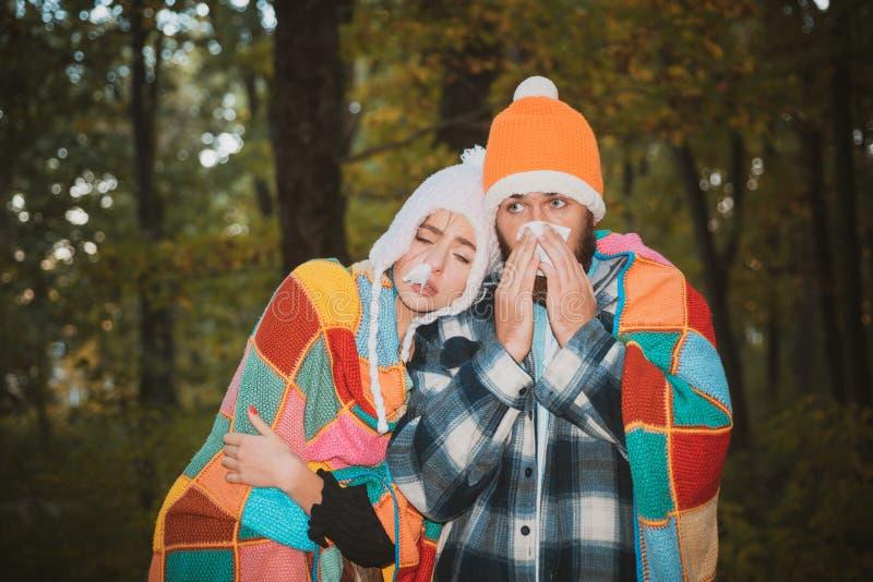 Zeigen von den kranken Paaren, die am Herbstpark niesen Mädchen mit Taschentuch und niesendem Jungen im Herbstpark Kranker Paarfa stockbild
